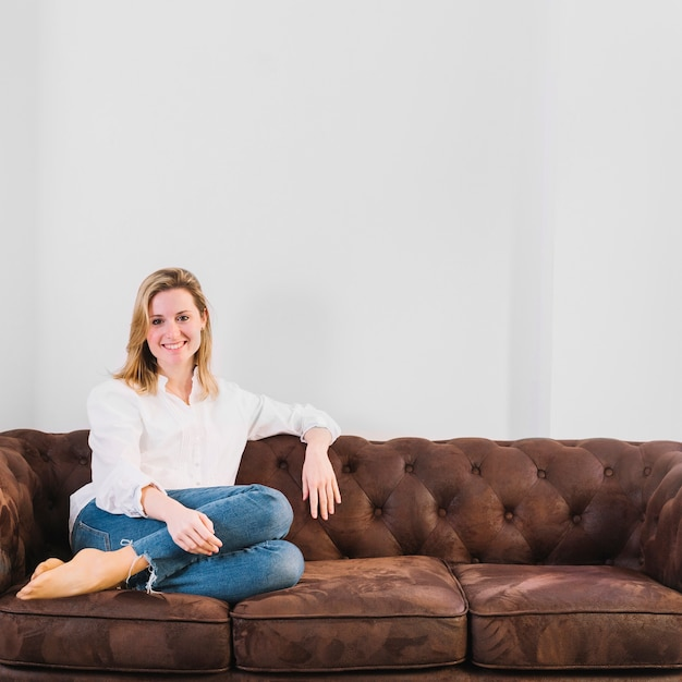 Mujer sonriente en el sofá Foto gratis