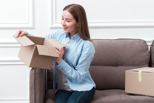 Mujer sonriente sosteniendo un paquete en el interior y sentado en el sofá Foto gratis