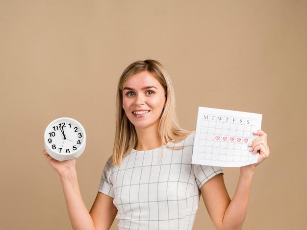 Mujer sonriente sosteniendo un reloj y su calendario de época Foto gratis