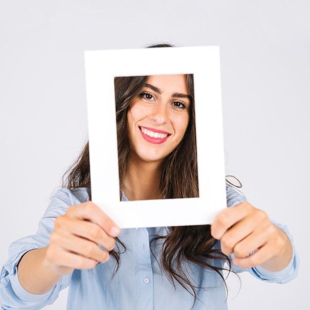 Mujer sonriente sujetando marco enfrente de cara Foto gratis