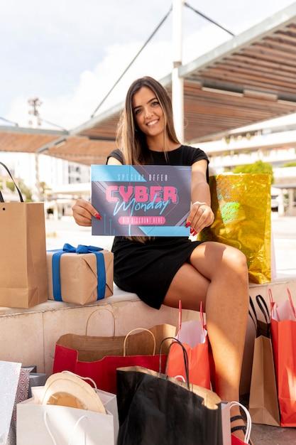 Mujer sonriente con tarjeta promocional Foto gratis