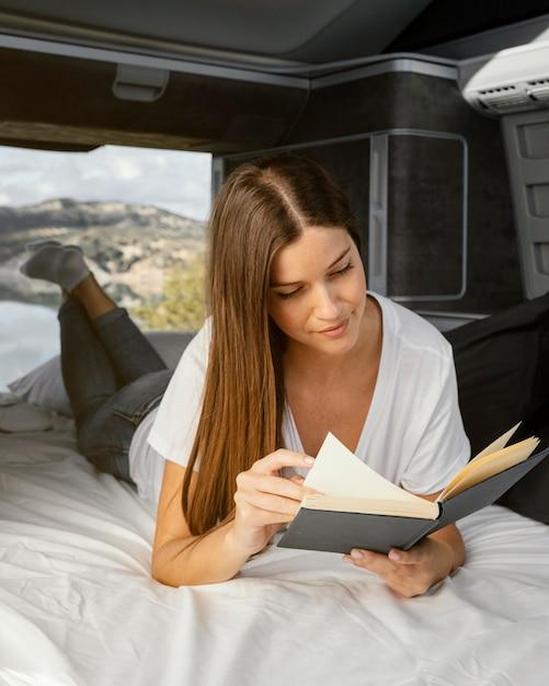 Mujer sonriente de tiro completo leyendo Foto gratis