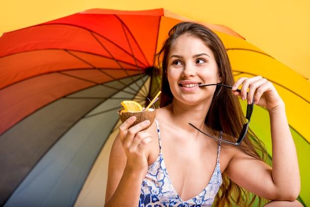 Mujer sonriente en traje de baño con bebida Foto gratis