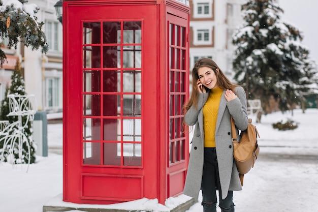 Mujer sonriente en traje elegante hablando por teléfono inteligente mientras está de pie cerca de la cabina telefónica británica en invierno. foto al aire libre de mujer morena complacida en abrigo de moda con mochila marrón durante la caminata. Foto gratis