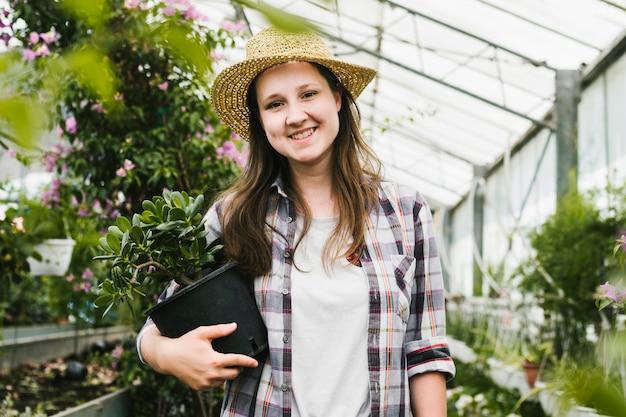 Mujer sonriente de la vista delantera en el invernadero Foto gratis