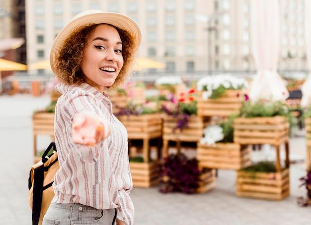 Mujer sonriente de vista lateral sosteniéndola junto a ella Foto gratis