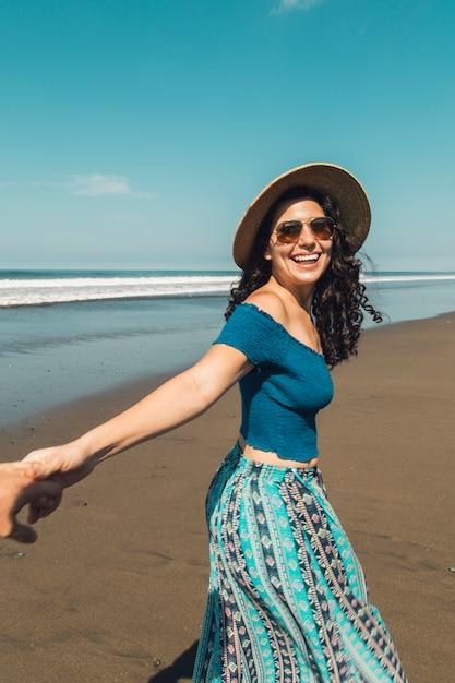 Mujer con sonrisa feliz sosteniendo la mano del hombre y caminando en la playa Foto gratis