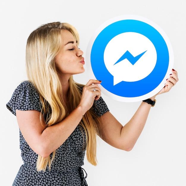 Mujer soplando un beso a un icono de facebook messenger Foto gratis