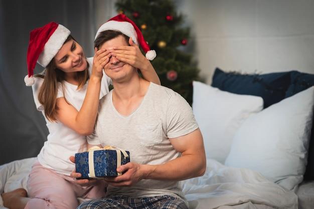 Mujer sorprendente hombre con regalo en dormitorio Foto gratis
