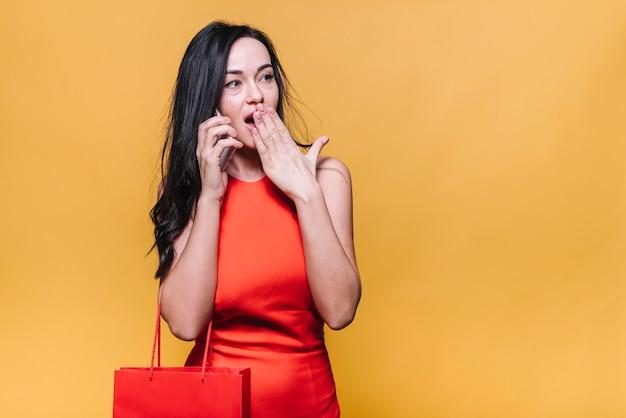 Mujer sorprendida hablando por teléfono mientras compra Foto gratis