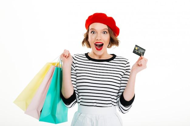 Mujer sorprendida de jengibre con paquetes con tarjeta de crédito y mirando a la cámara sobre gris Foto gratis