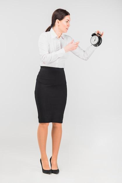Mujer sorprendida mirando el reloj de alarma en la mano Foto gratis