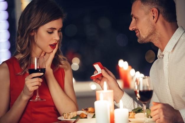 Mujer sorprendida mirando a su hombre dando su caja con anillo de compromiso Foto gratis