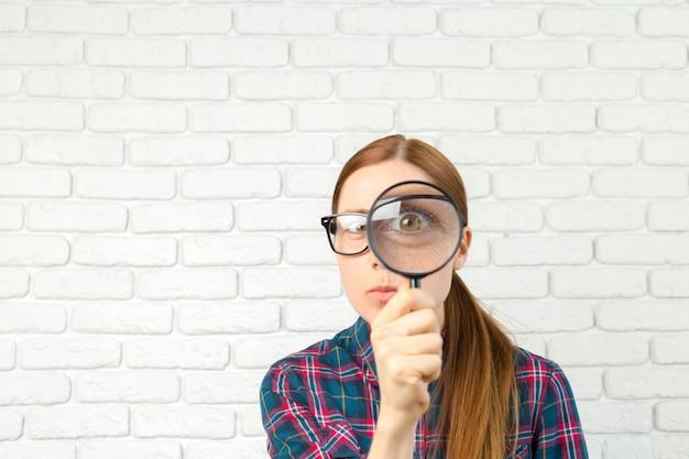 Mujer sorprendida mirando a través de una lupa. Foto Premium