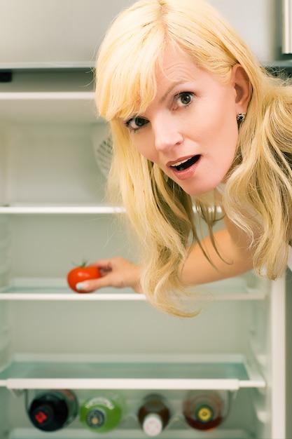 Mujer sorprendida con una nevera vacía Foto Premium