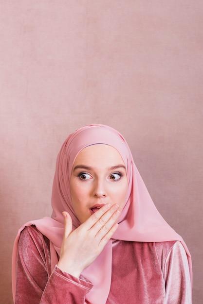 Mujer sorprendida que cubre los labios con la palma contra el fondo coloreado Foto gratis