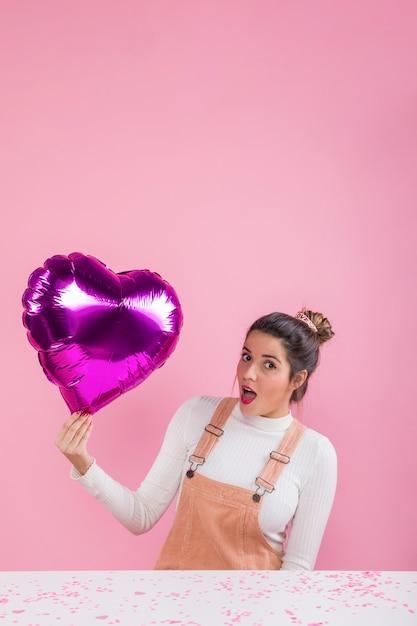 Mujer sorprendida que sostiene el globo del corazón en la mano Foto gratis