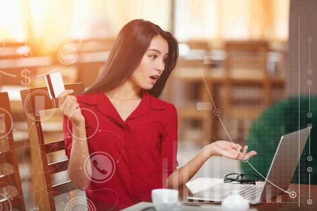 Mujer sorprendida con una tarjeta en la mano Foto gratis