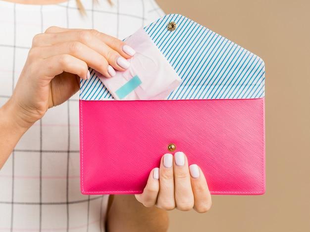Mujer sosteniendo una almohadilla y una billetera rosa Foto gratis