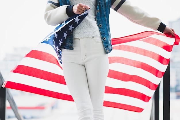 Mujer sosteniendo bandera americana desplegada detrás de las piernas Foto gratis