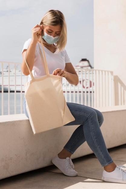 Mujer sosteniendo una bolsa reciclable vista lateral Foto gratis