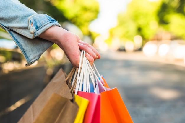 Mujer sosteniendo bolsas de compras en la mano Foto gratis