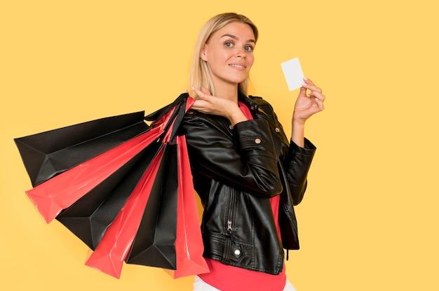 Mujer sosteniendo bolsas de compras rojas y negras para ventas de viernes negro Foto gratis