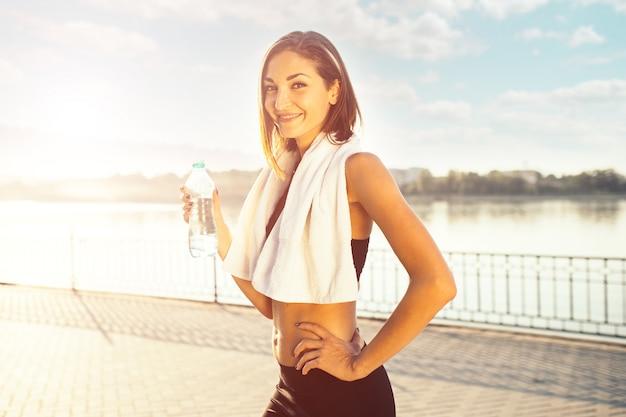 Mujer sosteniendo una botella de agua y una toalla Foto gratis