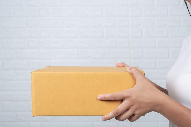 Mujer sosteniendo una caja de correos marrón hizo gestos con lenguaje de señas. Foto gratis