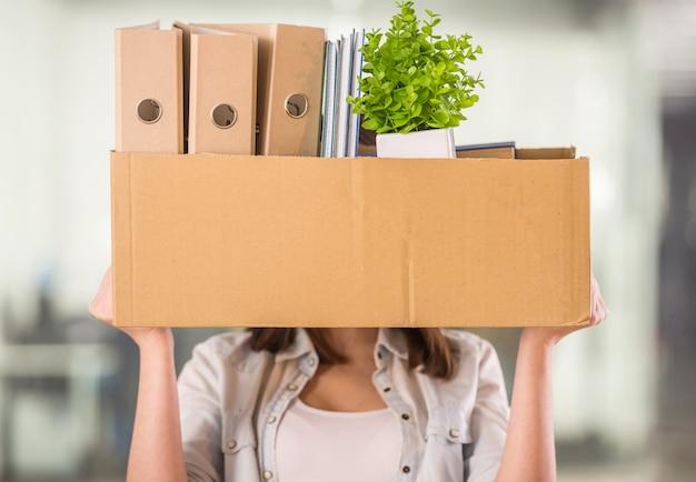 Una mujer sosteniendo una caja en una oficina. Foto Premium