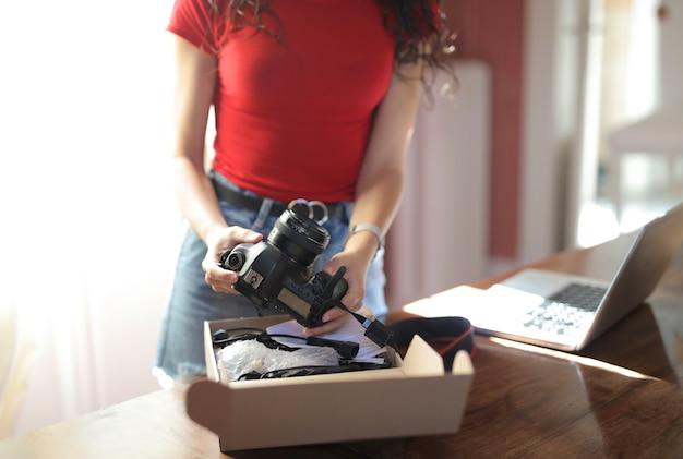 Mujer sosteniendo una cámara con un cuaderno sobre la mesa Foto gratis