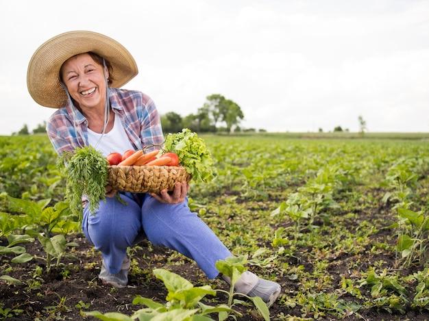 Mujer sosteniendo una canasta llena de verduras con espacio de copia Foto gratis