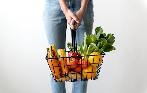 Mujer sosteniendo una canasta de verduras Foto gratis