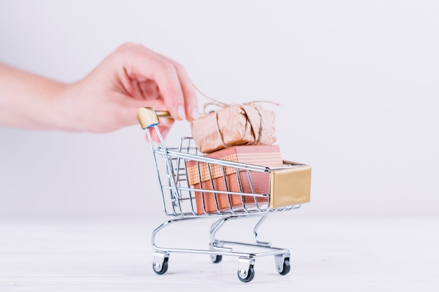 Mujer sosteniendo un carrito de supermercado con cajas de regalo Foto gratis