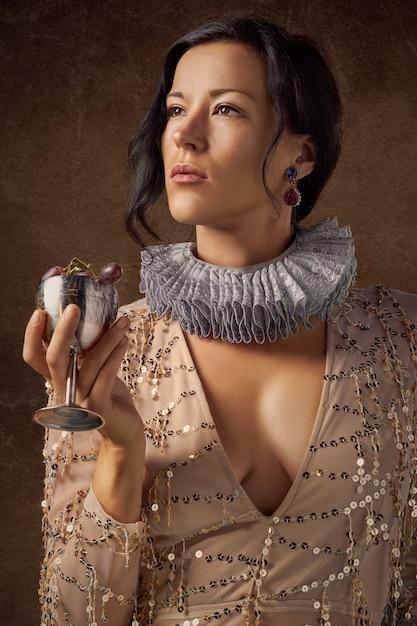 Mujer sosteniendo copa de vino de plata con uvas moradas Foto gratis