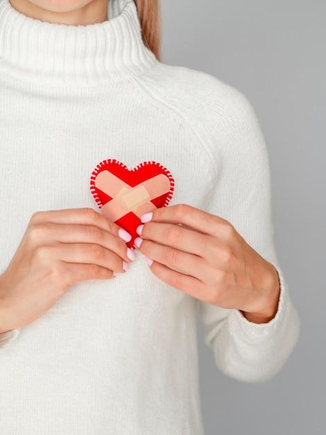 Mujer sosteniendo corazón con tiritas Foto gratis