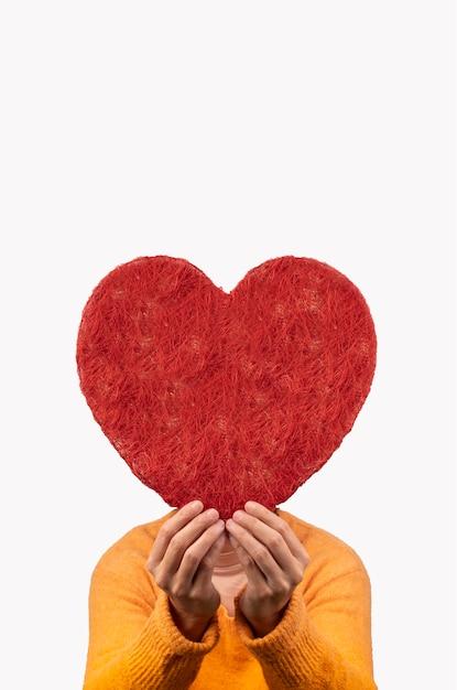 Mujer sosteniendo un gran corazón entre sus manos, concepto de día de san valentín Foto Premium