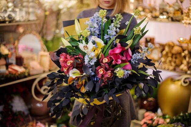 Mujer sosteniendo un hermoso ramo de orquídeas, lirios y hermosas hojas. Foto Premium