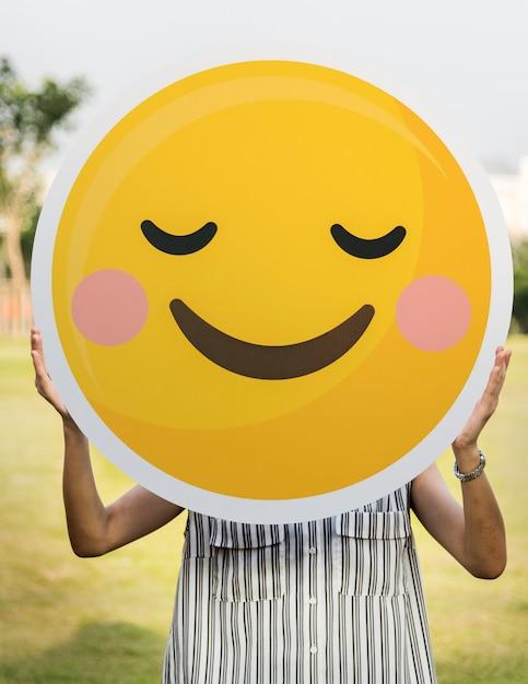Mujer sosteniendo un icono de cara sonriente Foto gratis