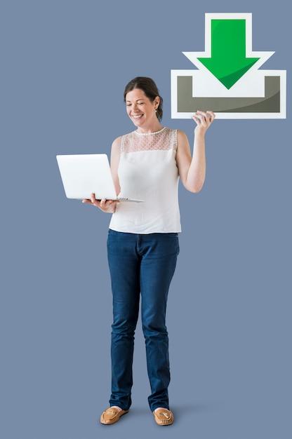 Mujer sosteniendo un icono de descarga y una computadora portátil Foto gratis