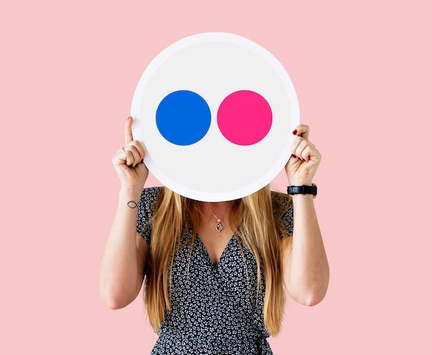 Mujer sosteniendo un ícono de flickr Foto gratis