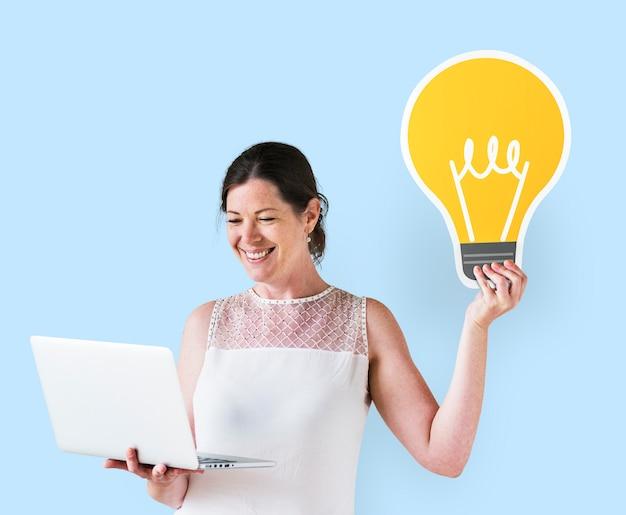 Mujer sosteniendo un icono de idea y usando una laptop Foto gratis
