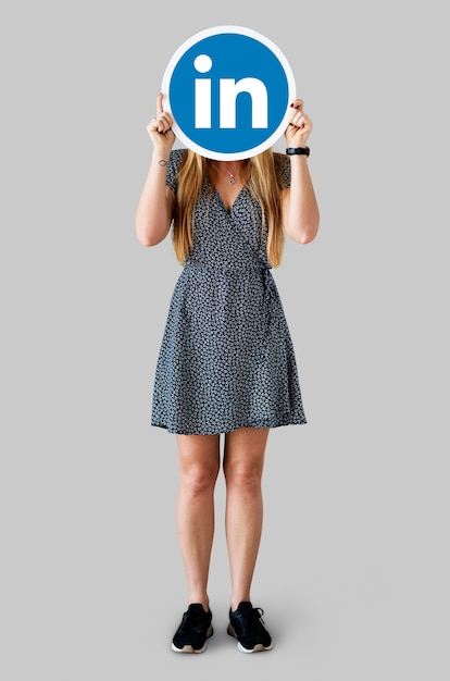 Mujer sosteniendo un icono de linkedin Foto gratis