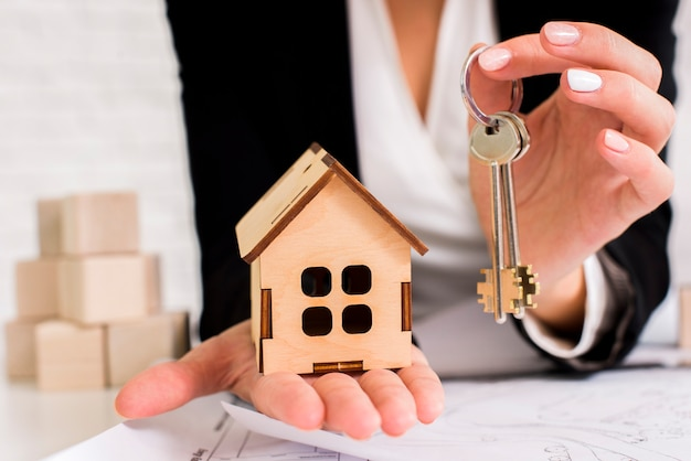 Mujer sosteniendo un juego de llaves con casa de madera Foto gratis