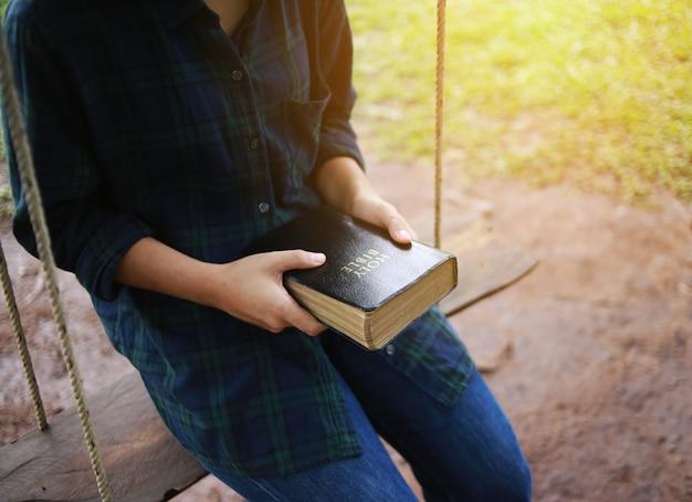Mujer sosteniendo un libro, la biblia, la naturaleza. Foto Premium