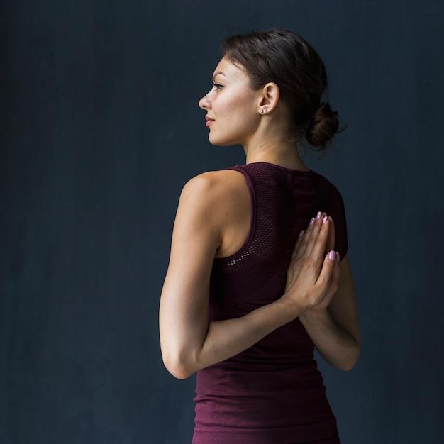 Mujer sosteniendo la mano en una pose de oración detrás de su espalda Foto gratis