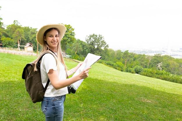Mujer sosteniendo un mapa y sonriendo Foto gratis