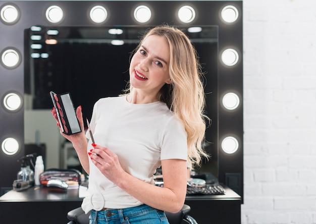 Mujer sosteniendo la paleta de colores con lápiz labial y pincel Foto gratis