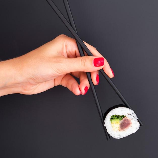Mujer sosteniendo en palillos un rollo de sushi Foto gratis