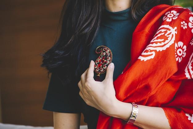 Mujer sosteniendo un pasador de joyería con forma de buta Foto gratis